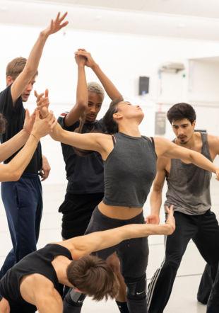 Un groupe de danseuses et danseurs en plein mouvement, portant des habits de répétitions. © GTG / Gregory Batardon